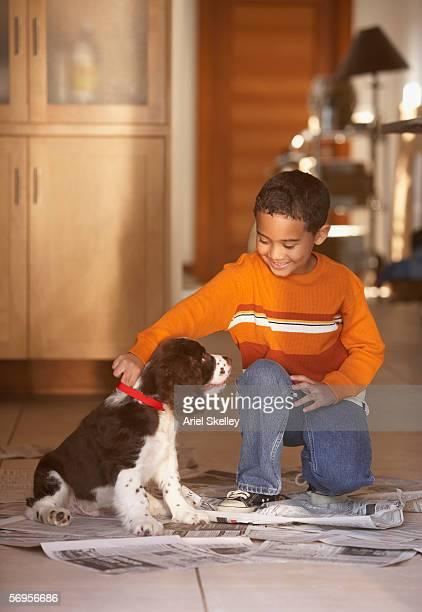 Boy with puppy on newspaper