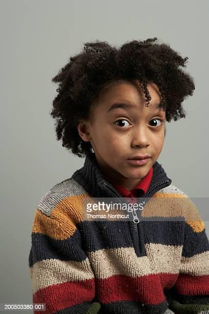 Boy (5-7) with raised eyebrows, portrait