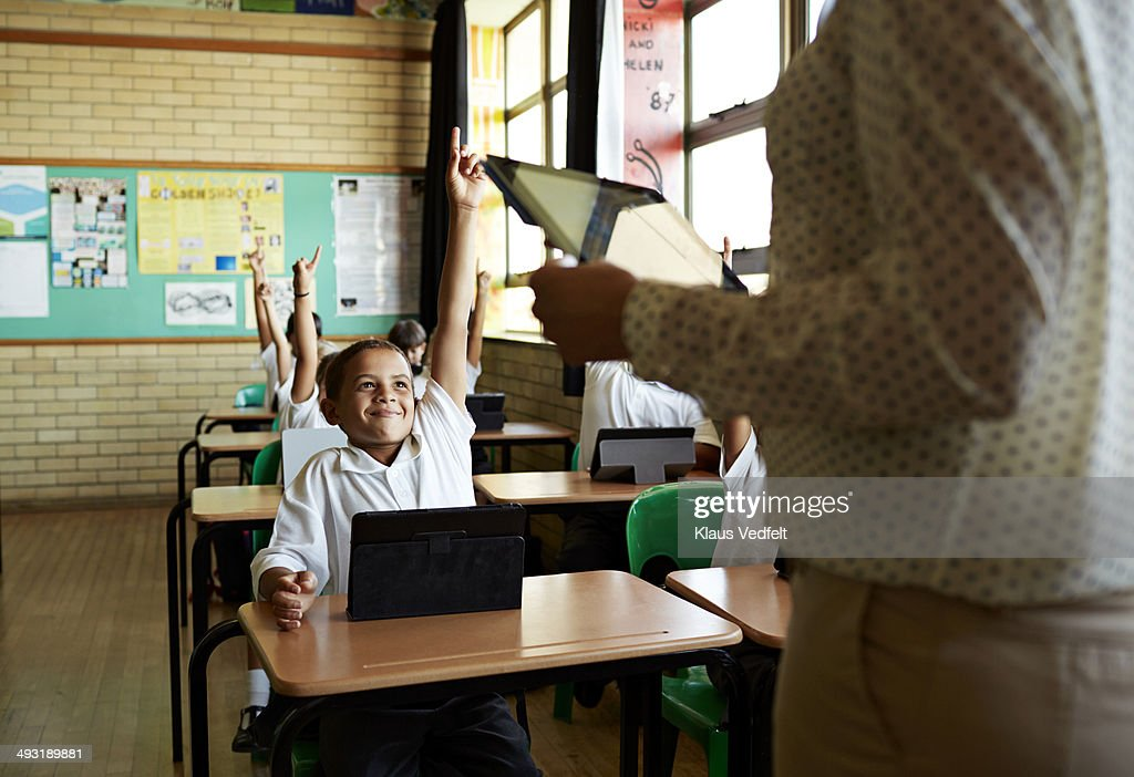 Boy with raised hand in classroom : Stock Photo