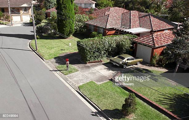 Boy with red balloon in front of house