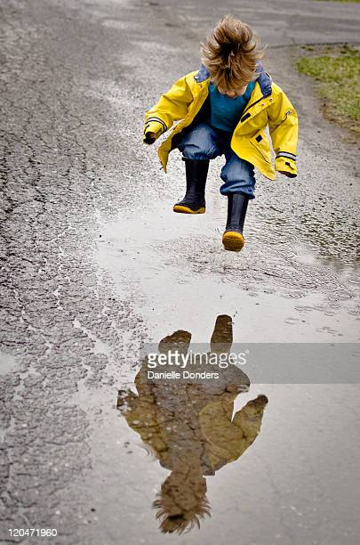 Boy with reflection jumping in puddle