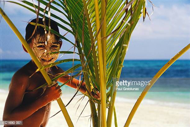 Boy (3-5) with sand on face hiding behind palm tree, Philippines