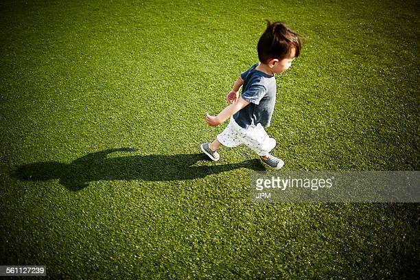 Boy with shadow running across the grass