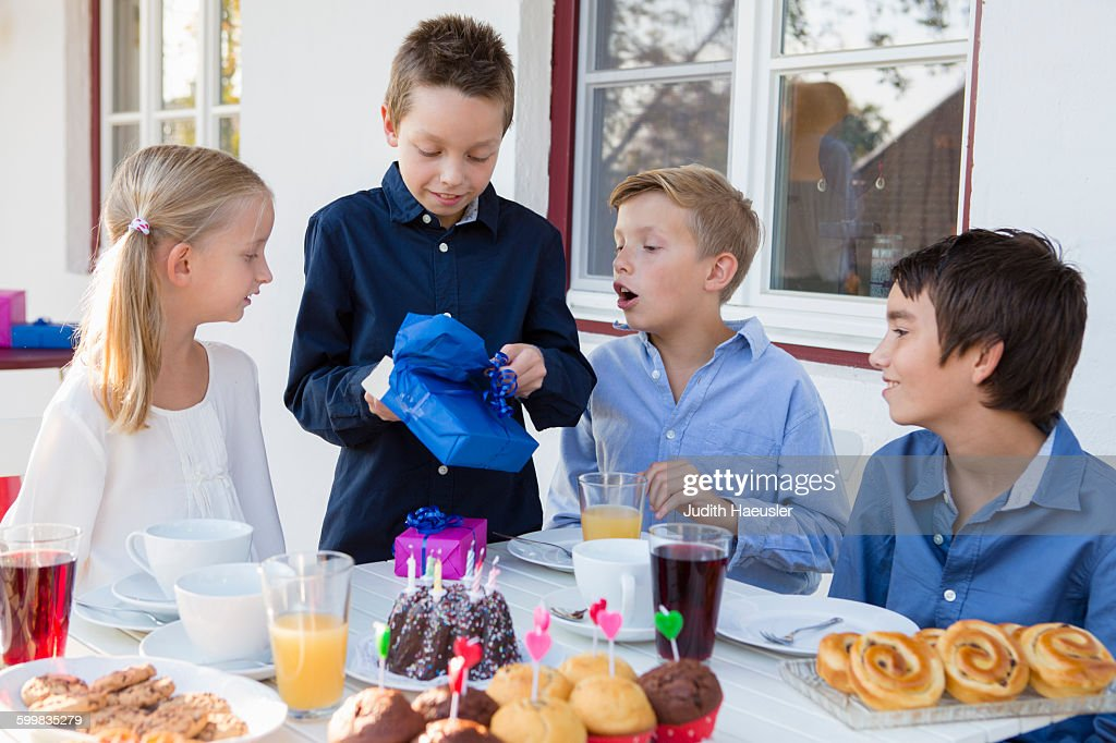 Boy With Siblings Unwrapping Birthday Gifts On Patio : Stock Photo