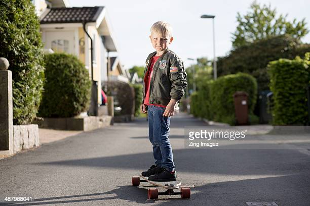 Boy with skateboard outdoors, portrait