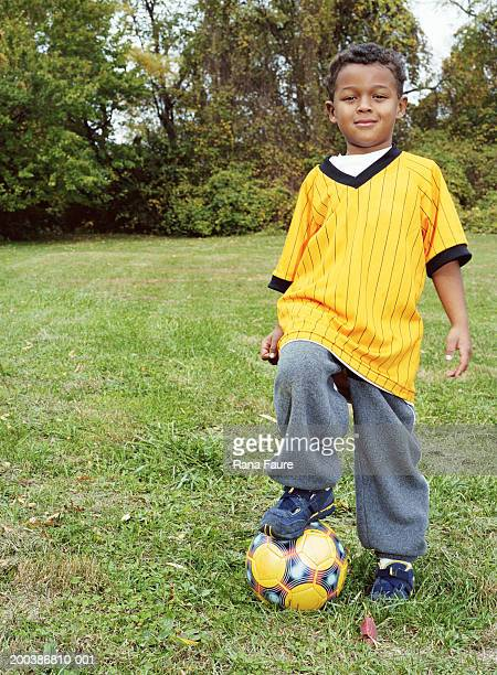 Boy (2-4) with soccer ball in field, portrait
