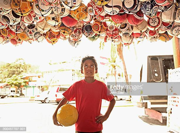 Boy (7-9) with soccer ball looking up at ball display in store