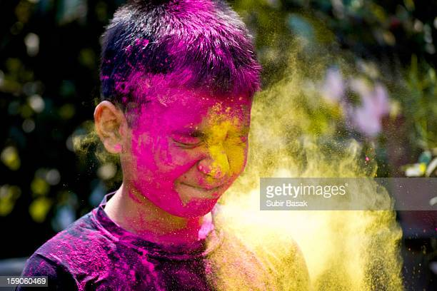 A boy with splashes of colour at holi festival