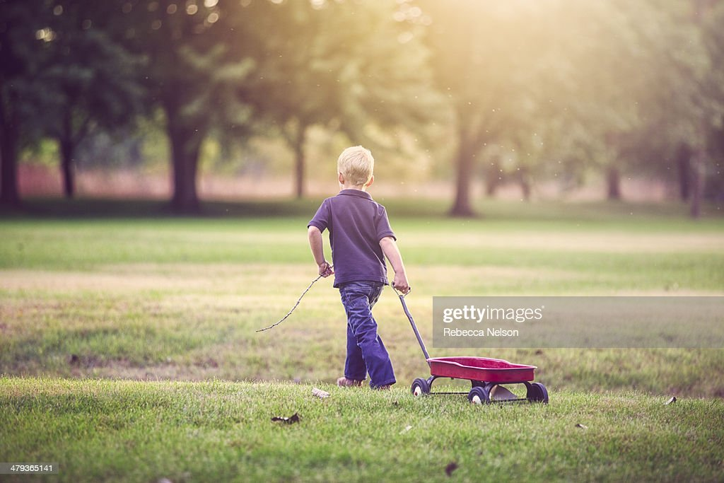 boy with stick pulling little, red wagon