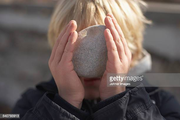 Boy with stone in front of his face