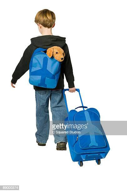 Boy with suitcase and backpack, rear view