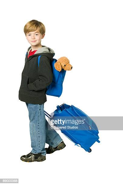 Boy with suitcase and backpack, side view