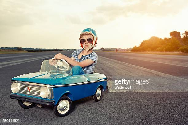 Boy with sunglasses in pedal car on race track