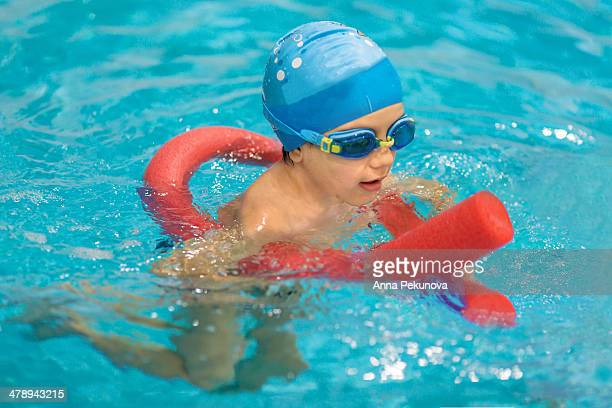 Boy with swim hat and glasses in swimming pool