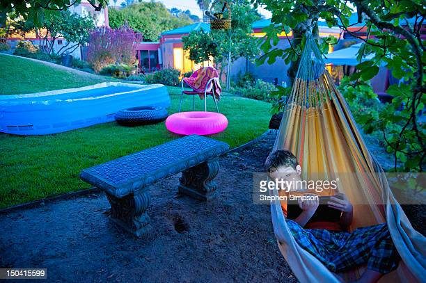 boy, 7, with tablet computer in backyard hammock