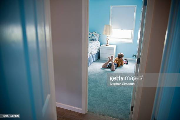 boy with tablet computer on floor in blue room