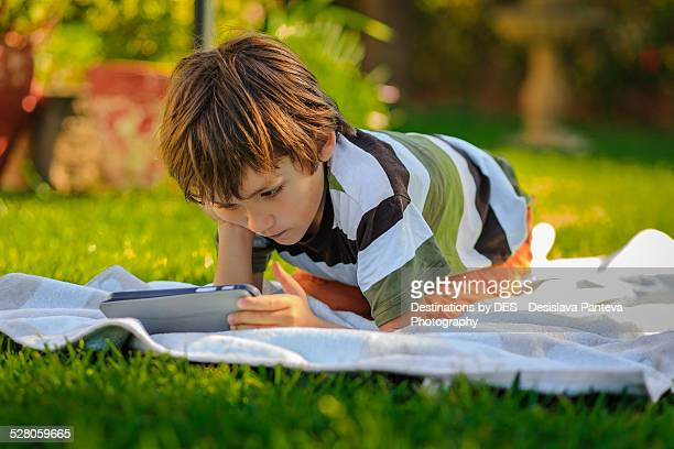 Boy with tablet in a garden