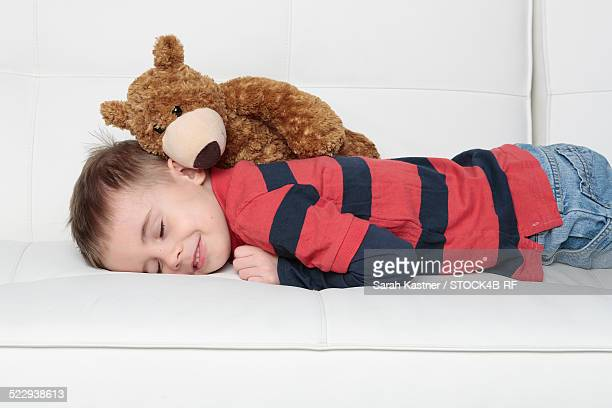 Boy with teddy bear lying on couch