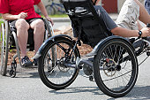 Boy with tendonitis on bike and a woman with degenerative hip in a wheelchair