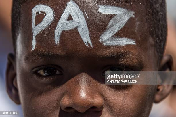 A boy with the word 'Peace' written on his front participates in a 'march for peace' at Rio de Janeiro's Alemao favela on April 4 2015 to protest...