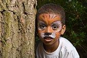 Boy with tiger makeup hiding behind tree