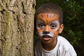 Boy with tiger makeup hiding behind tree