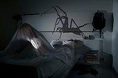 Boy with torch beneath blankets afraid of a spider