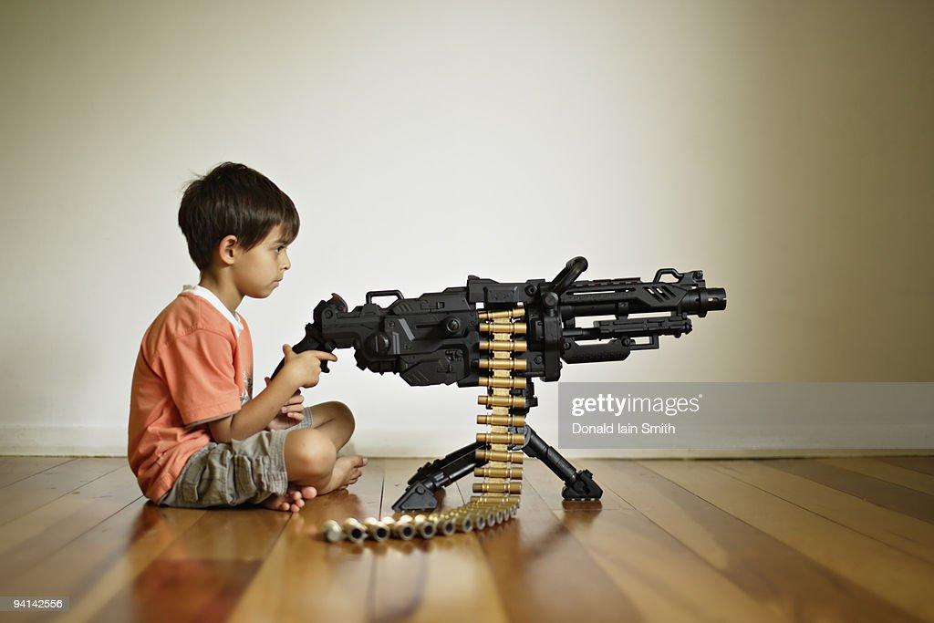 Boy with toy machine gun