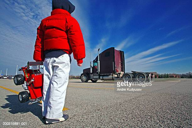 Boy (4-6) with toy truck looking at semi-truck, rear view