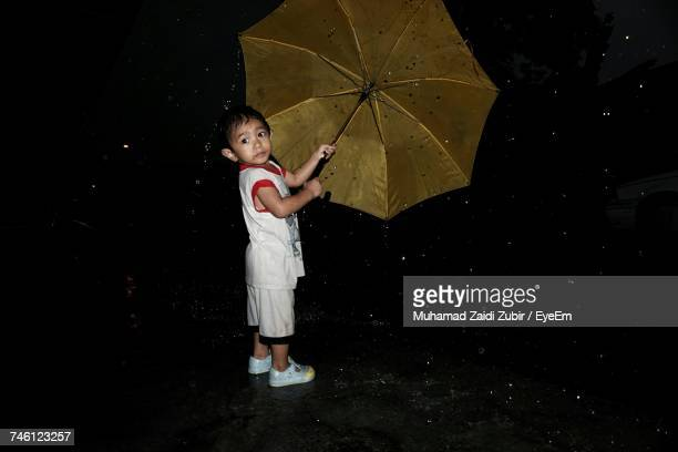 Boy With Umbrella Looking Away In Rain While Standing On Road During Night