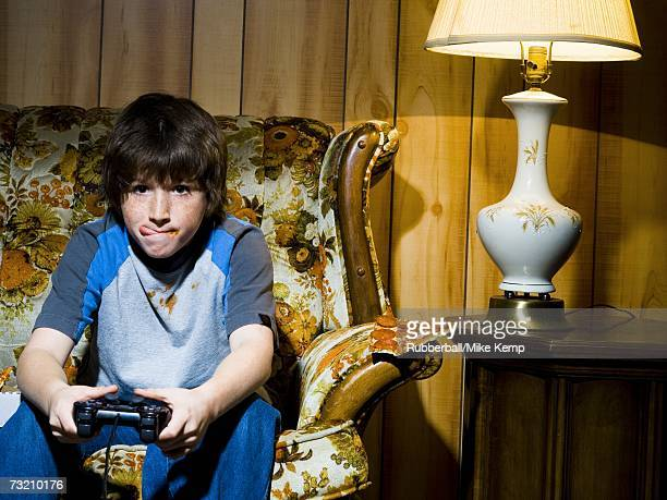 Boy with video game controller on sofa