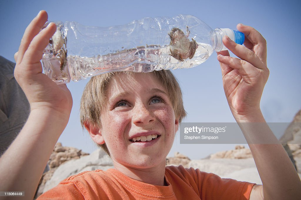 boy with water bottle with frogs in it : Stock Photo