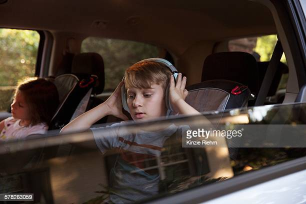 Boy with younger sister listening to headphones in car back seat