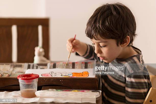 Boy wondering which color to use for painting
