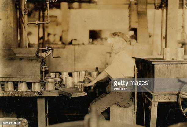 Boy working at an American canning machine with open gearing 1909 Baltimore Maryland Published 1909 July 7