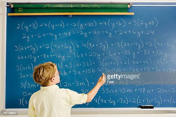 Boy Working on Equations on Blackboard