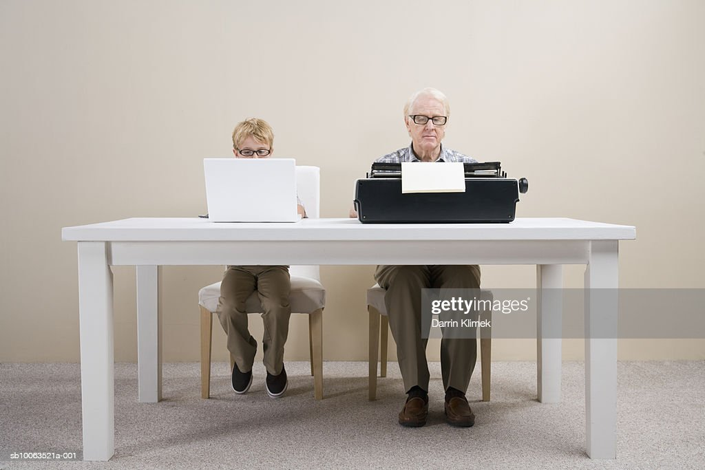 Boy (10-11) working on laptop and man working on typewriter sitting at table