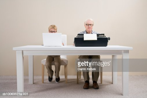 Boy (10-11) working on laptop and man working on typewriter sitting at table : Stock Photo