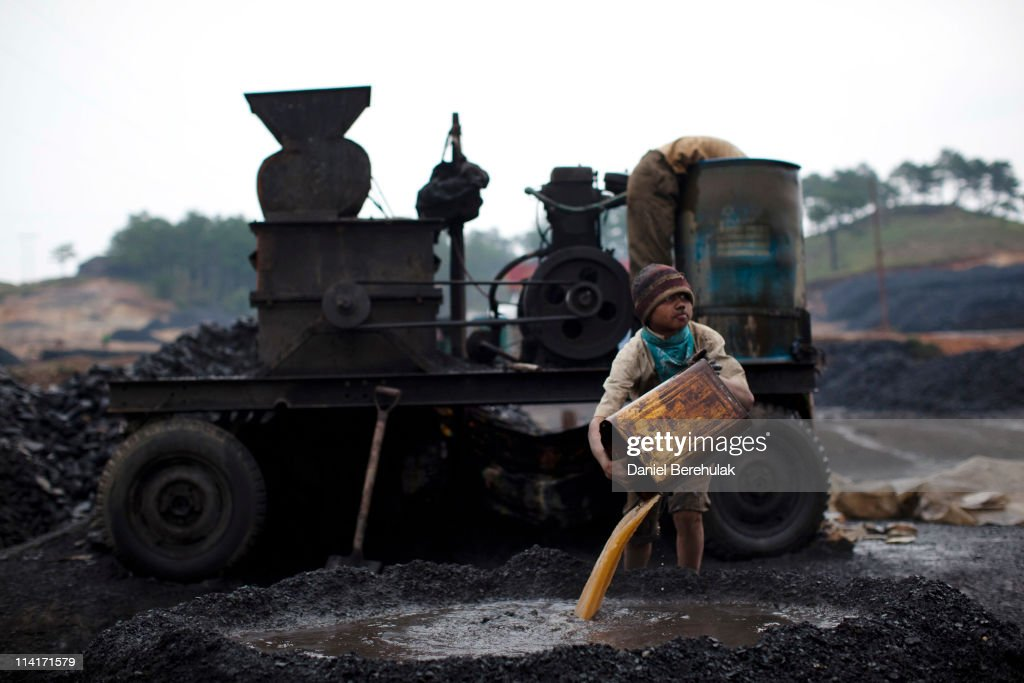 A boy works at a coal depot on April 16, 2011 near to Lad Rymbai, in the district of Jaintia Hills, India. Local schools in the area, providing free tuition, find it difficult to convince parents of the benefits of education, as children are seen as sources of income. The lure of the mines is stronger than that of the classroom. The Jaintia hills, located in India's far North East state of Meghalaya, miners descend to great depths on slippery, rickety wooden ladders. Children and adults squeeze into rat hole like tunnels in thousands of privately owned and unregulated mines, extracting coal with their hands or primitive tools and no safety equipment. Workers can earn as much as 150 USD per week or 30,000 Rupees per month, significantly higher than the national average of 15 USD per day. After traversing treacherous mountain roads, the coal is delivered to neighbouring Bangladesh and to Assam from where it is distributed all over India, to be used primarily for power generation and as a source of fuel in cement plants. Many workers leave homes in neighbouring states, and countries, like Bangladesh and Nepal, hoping to escape poverty and improve their quality of life. Some send money back to loved ones at home, whilst many others squander their earnings on alcohol, drugs and prostitution in the dusty, coal mining towns like Lad Rymbai. Some of the labor is forced, and an Indian NGO group, Impulse, estimates that 5,000 privately-owned coal mines in Jaintia Hills employed some 70,000 child miners. The government of Meghalaya refuted this figure, claiming that the mines had only 222 minor workers. Despite the ever present dangers and hardships, children, migrants and locals flock to the mines hoping to strike it rich in India's wild east.