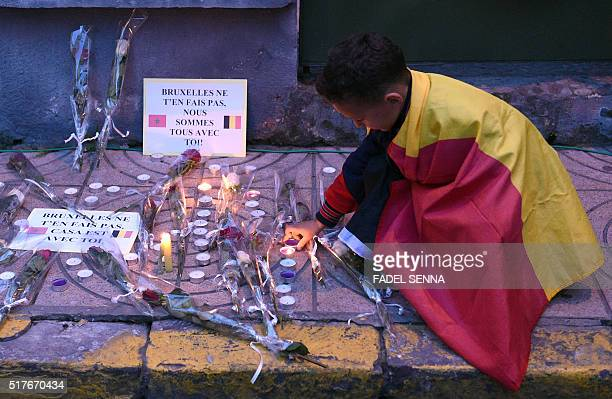 A boy wrapped in a Belgian flag lights a candle during a tribute to the victims of the Brussels attacks in Casablanca on March 26 four days after a...