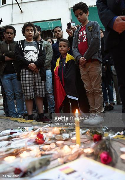 A boy wrapped in a Belgian flag stands in front of a makeshift memorial in tribute to the victims of the Brussels attacks in Casablanca on March 26...