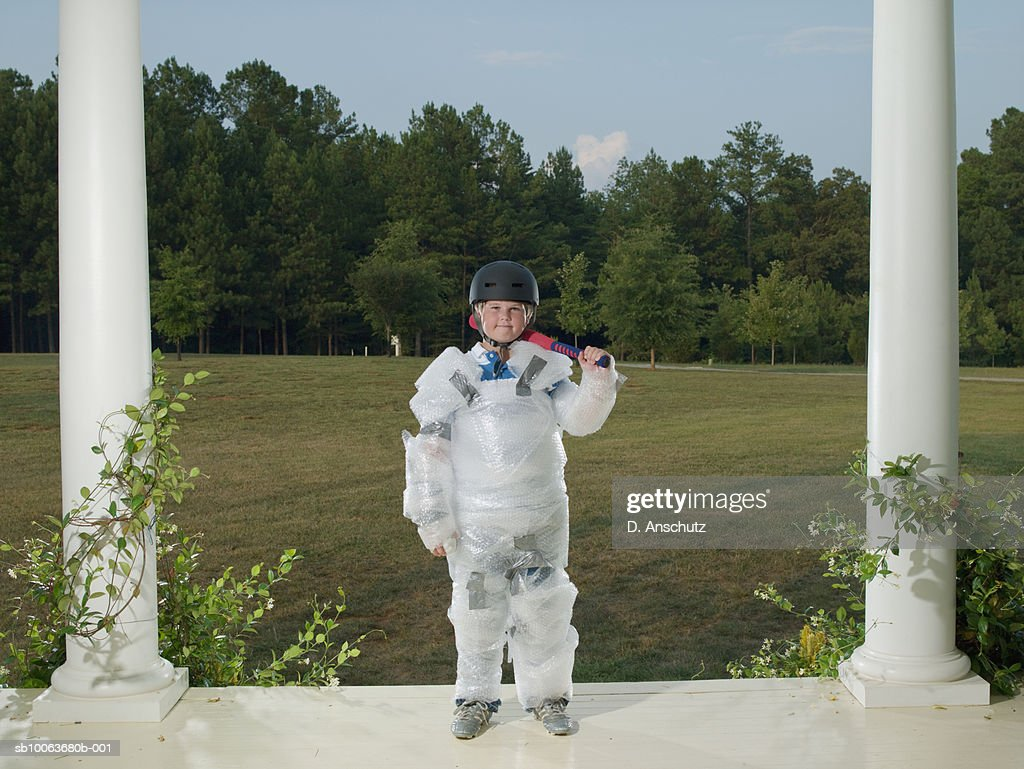 Boy (10-11) wrapped in bubble wrap, standing on porch with baseball bat