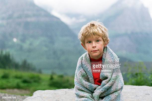 A boy wrapped in his blanket in glacier