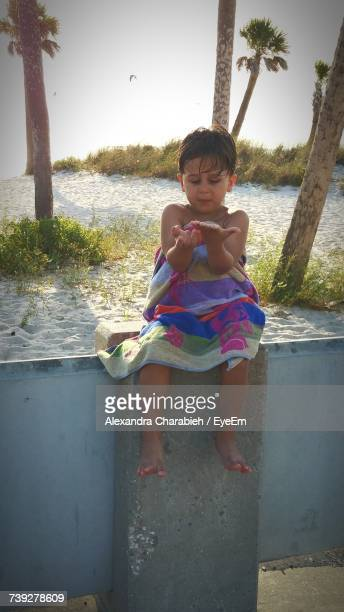 Boy Wrapped In Towel Looking At Hands While Sitting On Retaining Wall