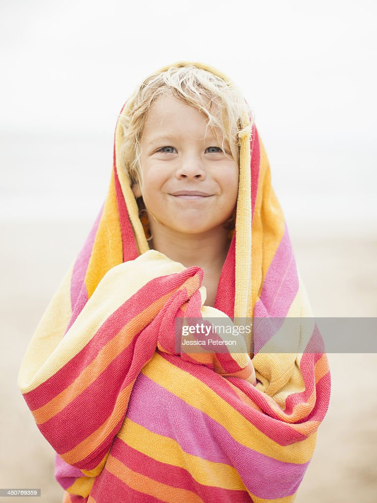 Boy (6-7) wrapped in towel on beach : Stock Photo