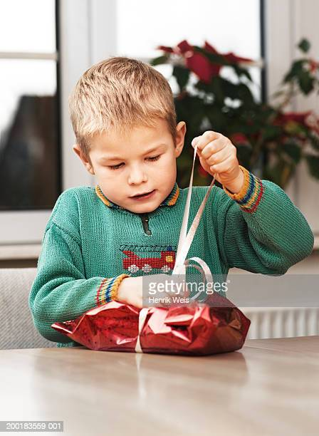 Boy (4-6) wrapping present at table, pulling ribbon
