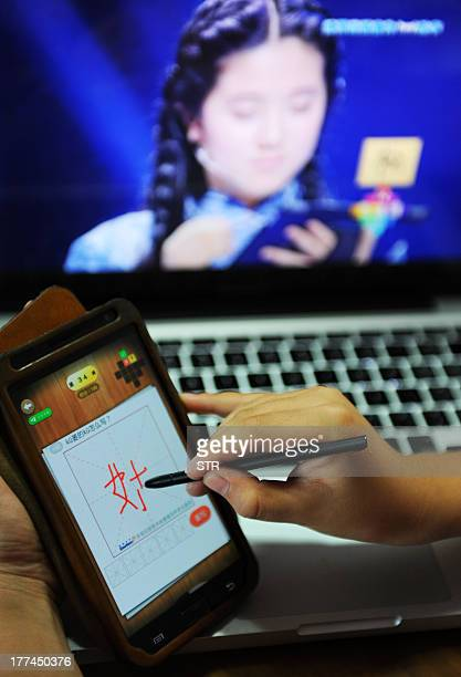 A boy writes a Chinese character on his cellphone as he watches a TV programme called 'hanzi yingxiong' Chinese characters hero at his home in...