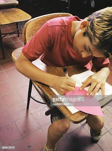 Boy writing in card