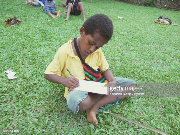 Boy Writing In Note Pad While Sitting At Grassy Field