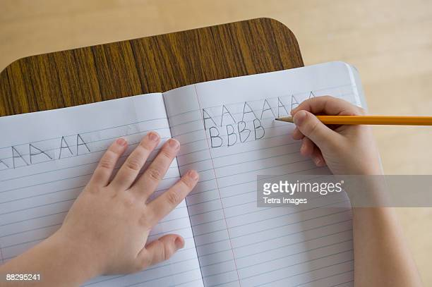 Boy writing letters in classroom